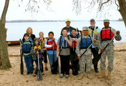 a group photo of youth, staff, and two U.S. Soldiers on the beach with their paddles and life jackets