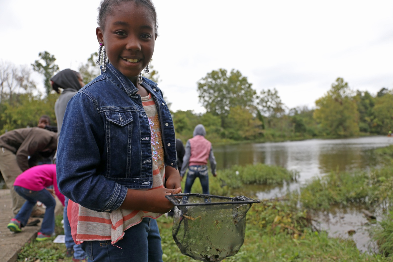 young girl uses a small net to catch some wildlife near a river