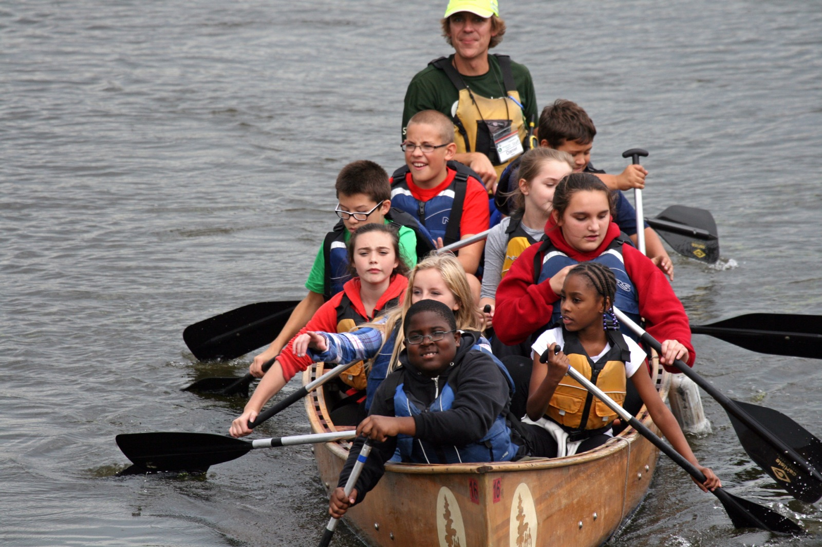 an action shot of 9 youth and a staff member paddling their canoe on the lake
