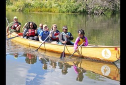 A group of participants test out their paddling skills on a sunny day on the river