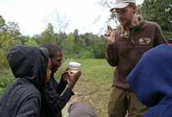 two youth learn about wildlife near the river with a staff member