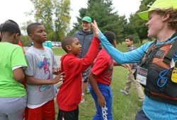 staff member and participants exchange  high five's after a successful day of canoeing