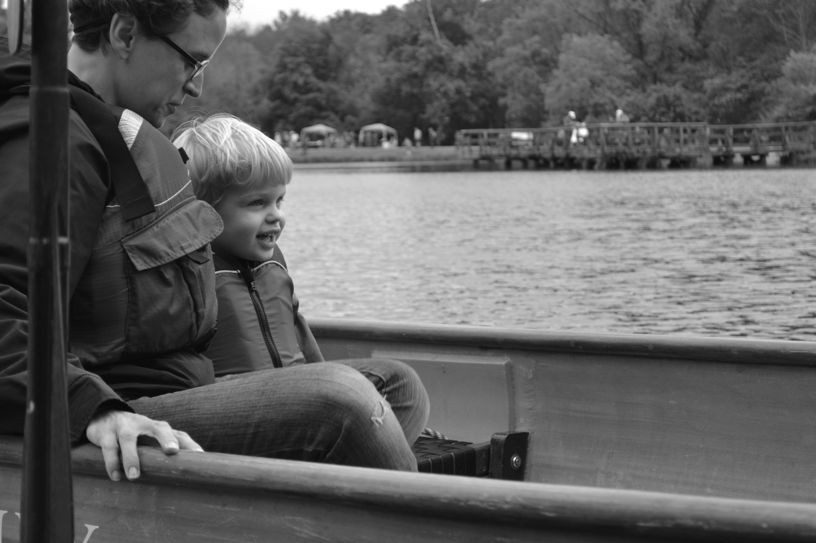 black and white photo of a young child and a mother sitting in the canoe next to shore