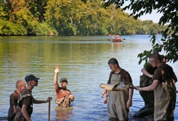 a group of six participants stand in the water with nets during a water quality testing activity