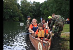 a group of participants load up in the canoe next the shore