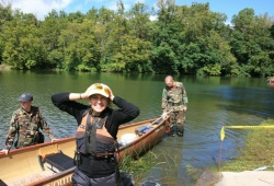 a staff member smiles for the camera as they get ready for a canoe ride