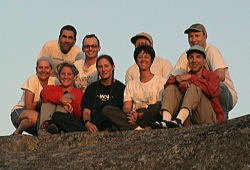 A group poses together on a rock on the shore of Lake Superior on the last night of the Isle Royale backpacking trip.