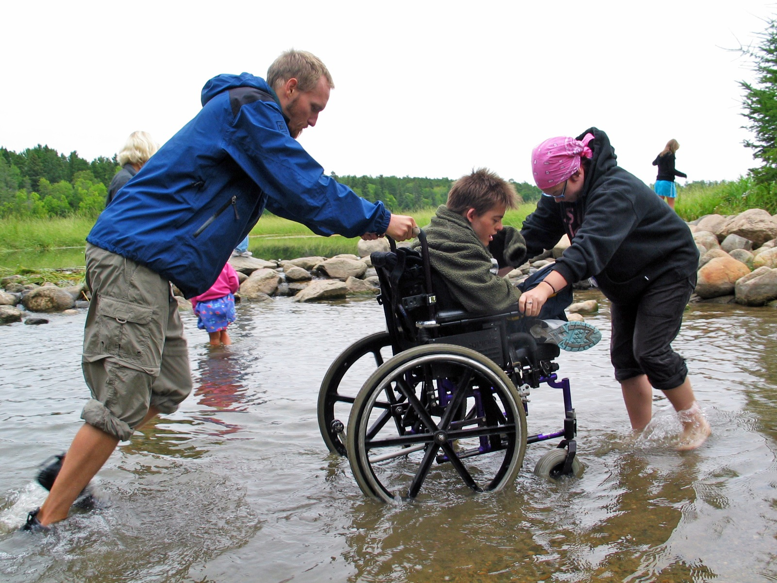 A participant using a wheelchair to crosses the Mississippi Headwaters with the help of fellow participants.
