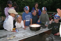 Kids gather around a picnic table to celebrate a birthday at the 4th of July in Itasca State Park.