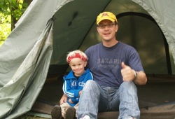 A father and son sit together in the doorway of a tent.