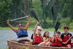 a group of 5 in the back of a Voyageur canoe raise their paddles above their head on the water