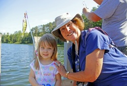 a young girl holds her fishing rod with a woman on a dock before fishing