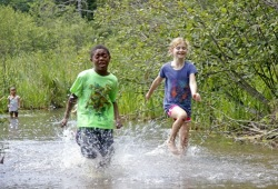 a young boy and girl race through the water