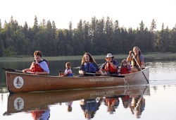 a group of six take a canoe out for a paddle in the evening on a calm lake