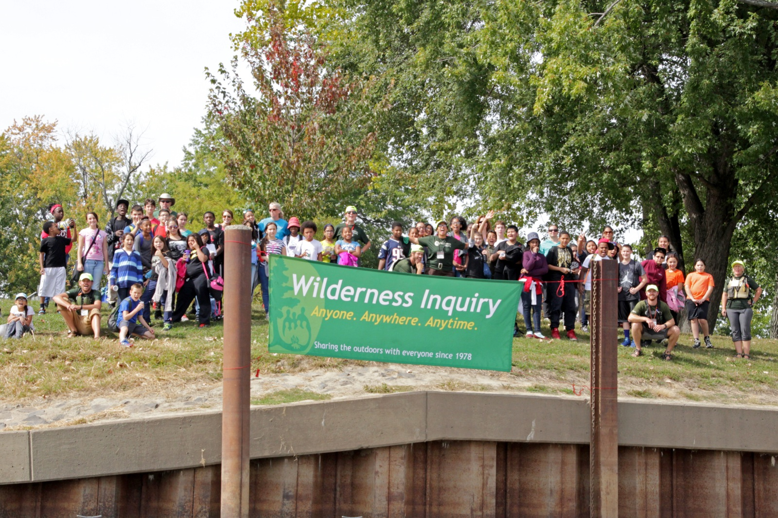 Large group of participants and staff smile behind a Wilderness Inquiry sign