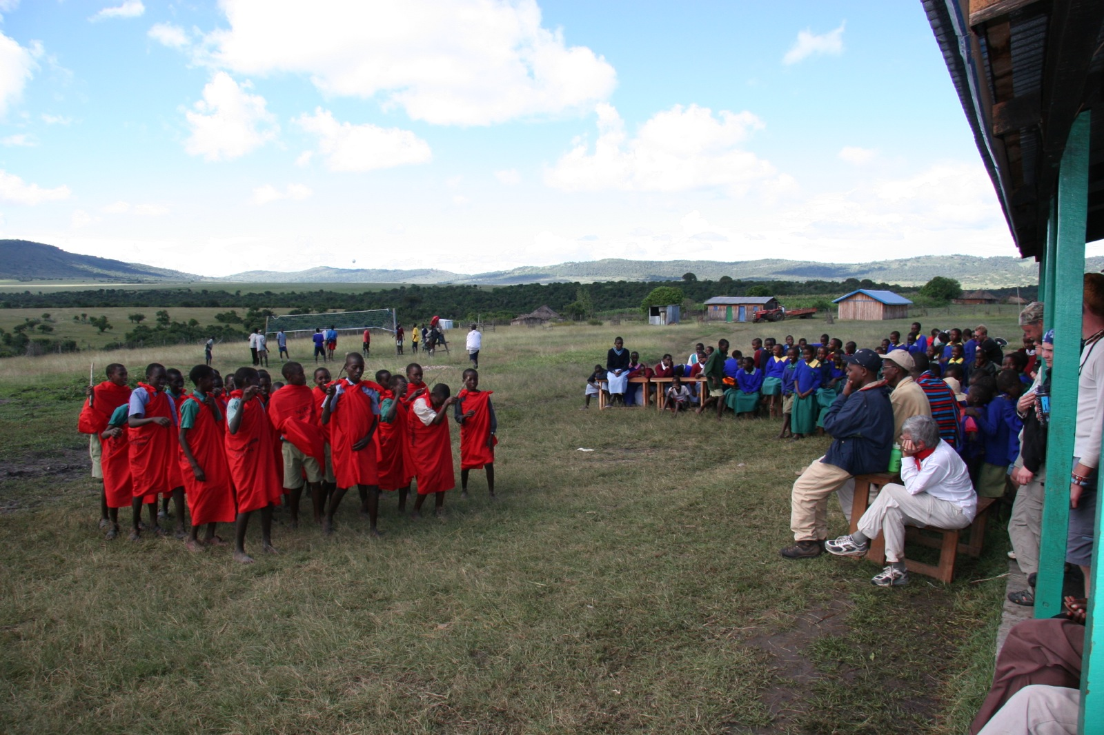 A group of Kenyan youth dressed in bright red cloths - the Naaroposa Primary School Choir - sings to American visitors who look on from under the overhang of a building.