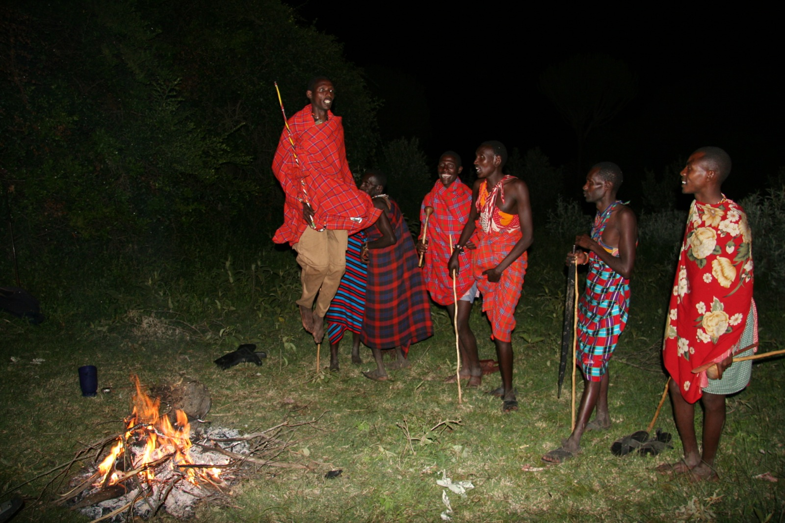 Maasai men in traditional dress showing their jumping skills by a campfire in the Kenya wilderness.