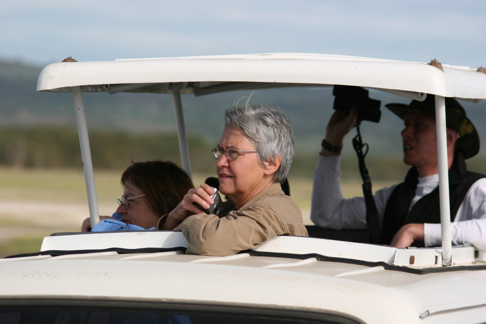 Three participants holding cameras and binoculars poke their heads out of a pop top safari van to look for wildlife.