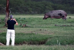 A participant attempts to get a closer photo of a hippo grazing near the Ewaso Nyiro River.