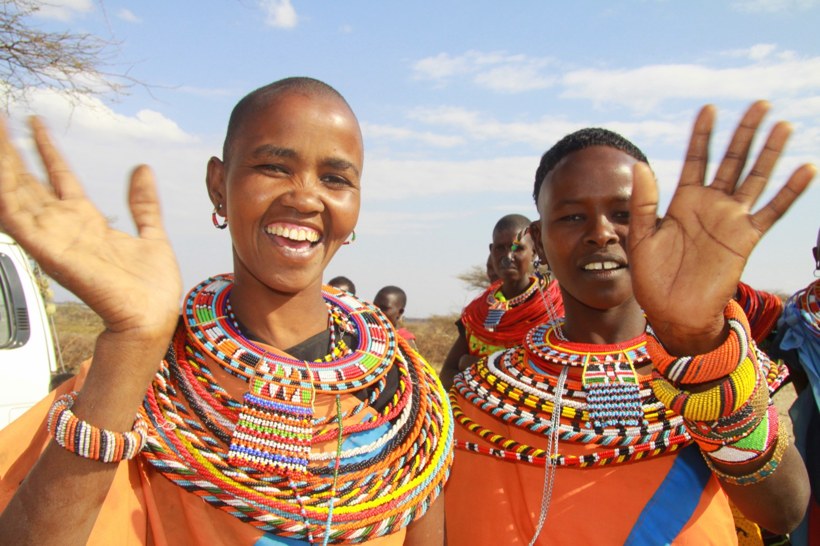 Two Masaai women wave to the camera showing us their colorful beaded necklaces and bracelets.