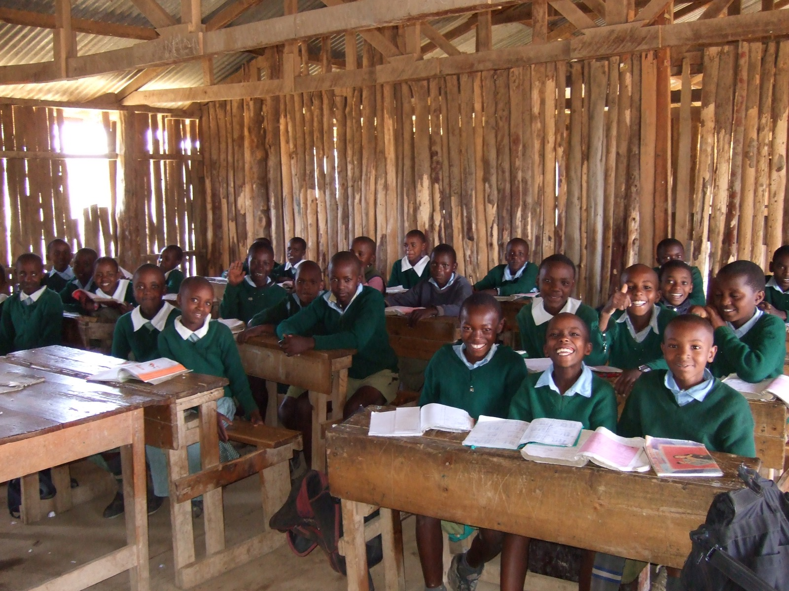 Smiling primary school children sit together at desks in their classroom, which used to be a horse stable.