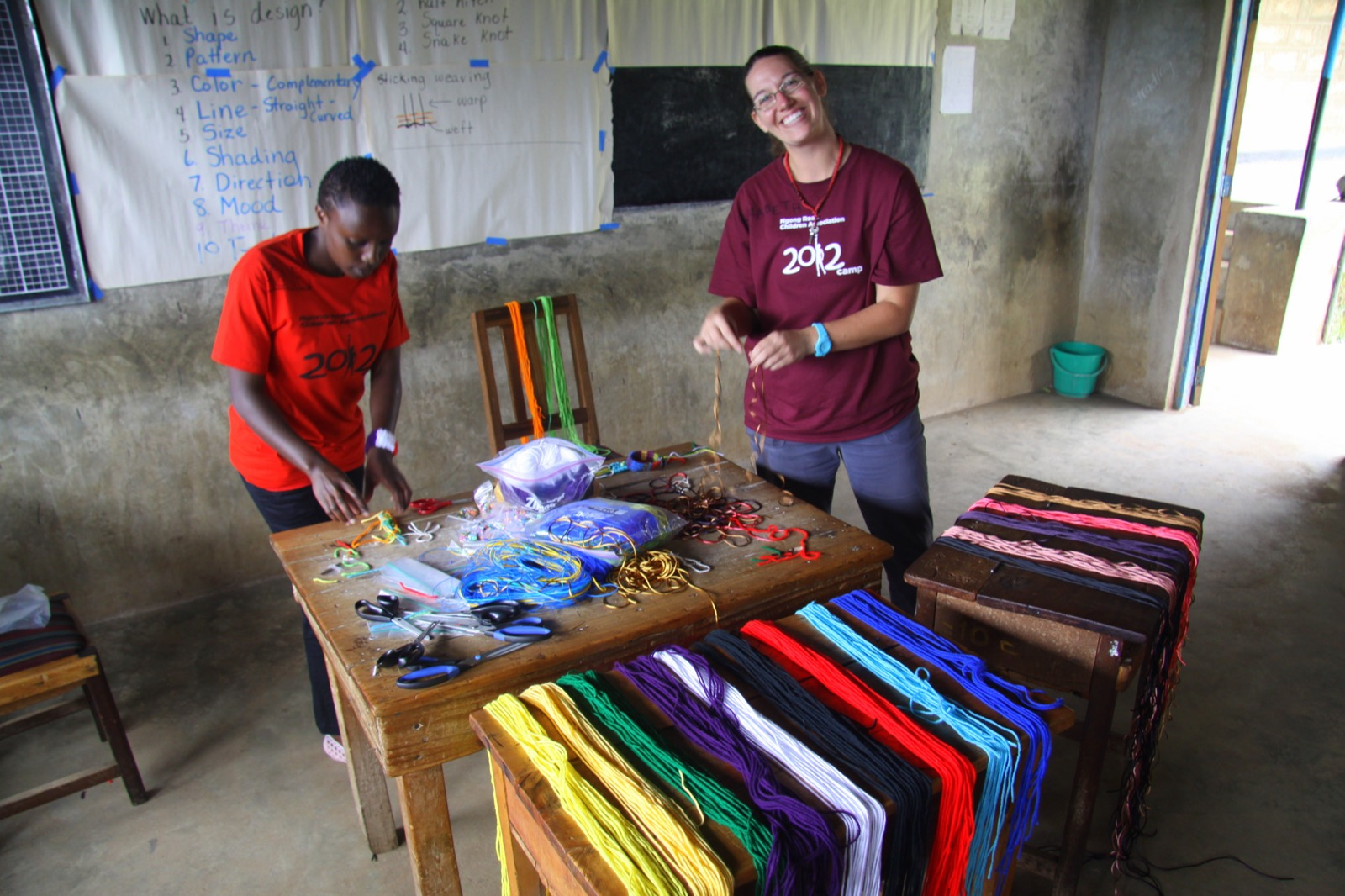 Two participants in red shirts stand next to tables covered with yarn, and smile.