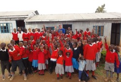 Wilderness Inquiry staff stand with sea of school children dressed in red sweaters in Kenya.