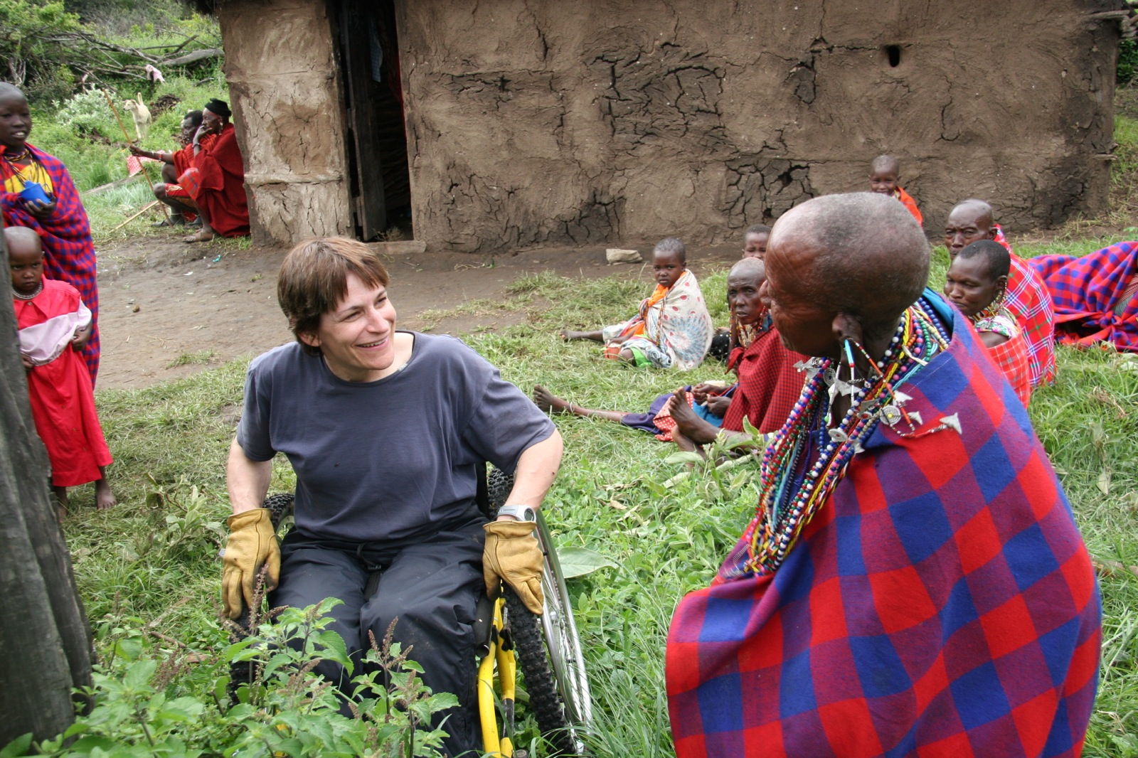 A participant interacts with a Maasai Koko, or grandmother, who is wrapped in a traditional red and blue plaid cloth.