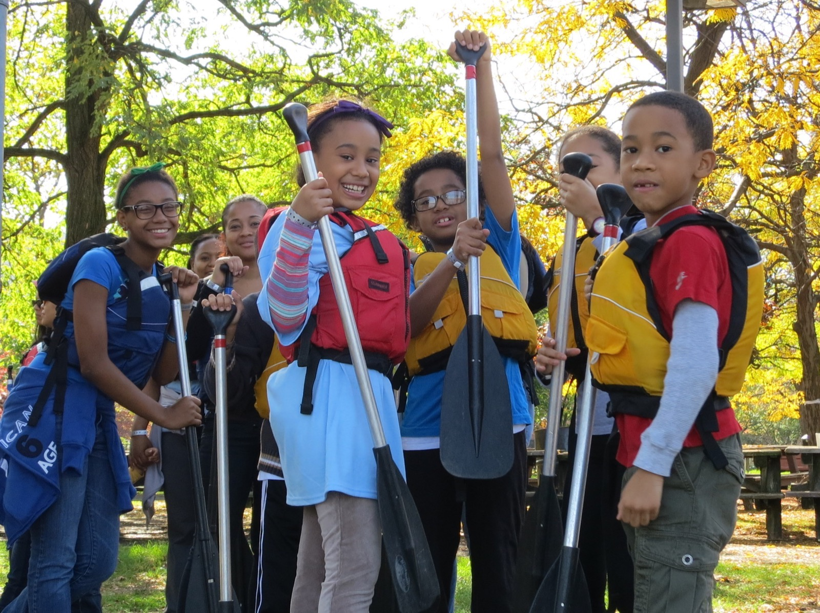 a group of young students wear their life jackets while holding their paddles waiting to get into a canoe