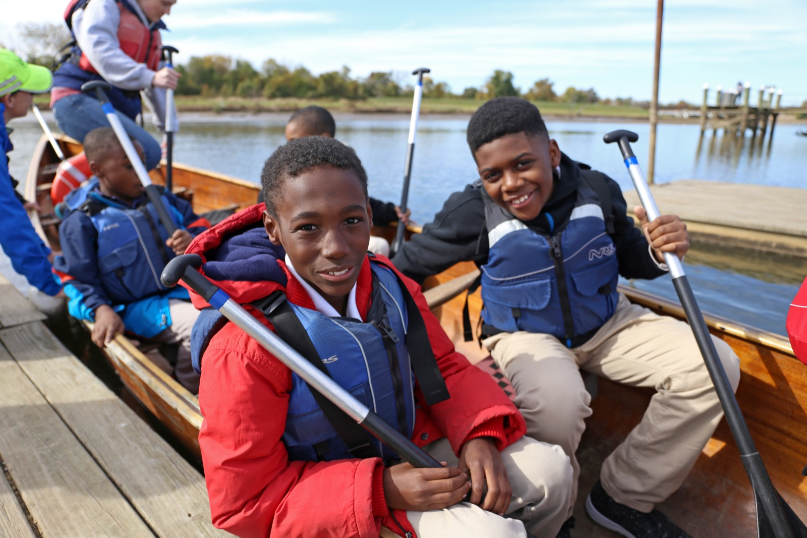 two youth smile for the camera in their canoe next to the dock