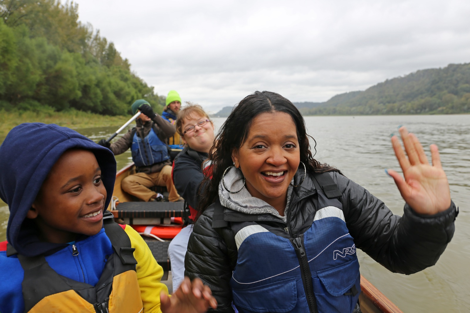 3 participants wave to the camera while in a canoe as they paddle along a wide river on a cloudy day