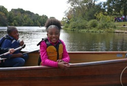 a girl sits in the bow of the canoe smiling for the camera with her life jacket on