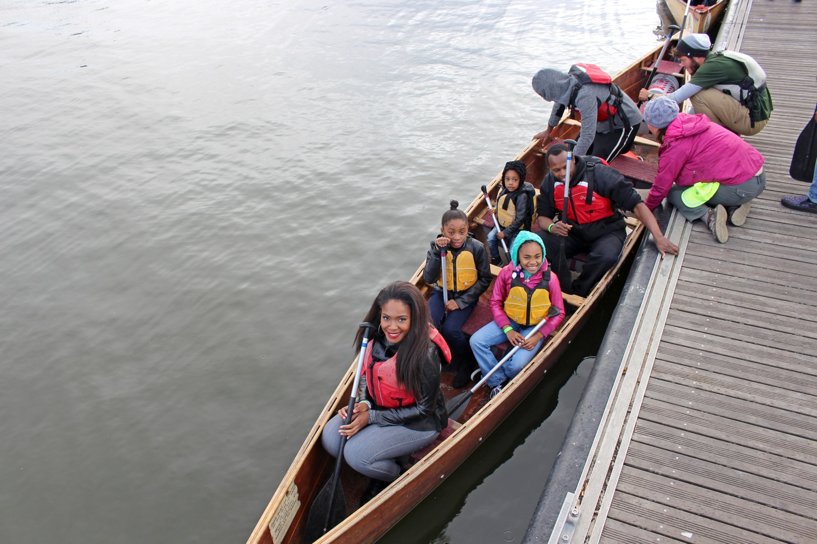 two staff members help participants load into a voyageur canoe beside a dock in Mankato