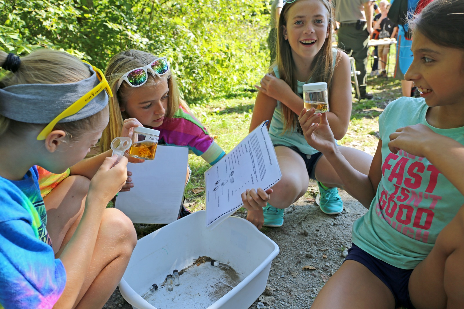 a group of 4 girls use magnify glasses to look close at jars of water