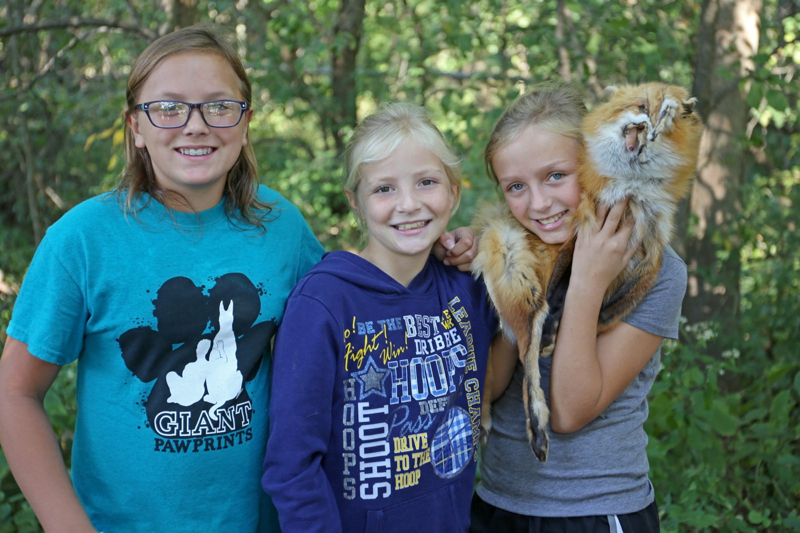 three girls hold the fur of a fox