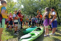 a group of youth gather around a kayak on land to learn how to kayak