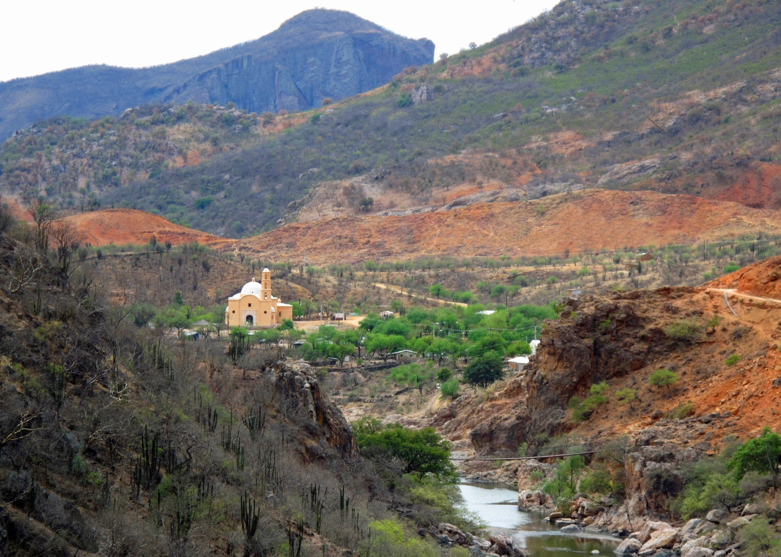 Beautiful view of the Lost Mission of Staevo church in Copper Canyon surrounded by rough terrain with cooper colored sand and green vegetation.
