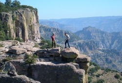 Two participants balance on rocks on top of Copper Canyon with sensational views of the canyon in the background.