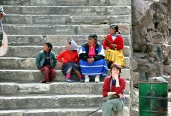 April sits on the steps while waiting for the Copper Canyon train next to a Tarahumara family.