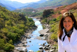 A woman smiles with a creek and green hills in the background.