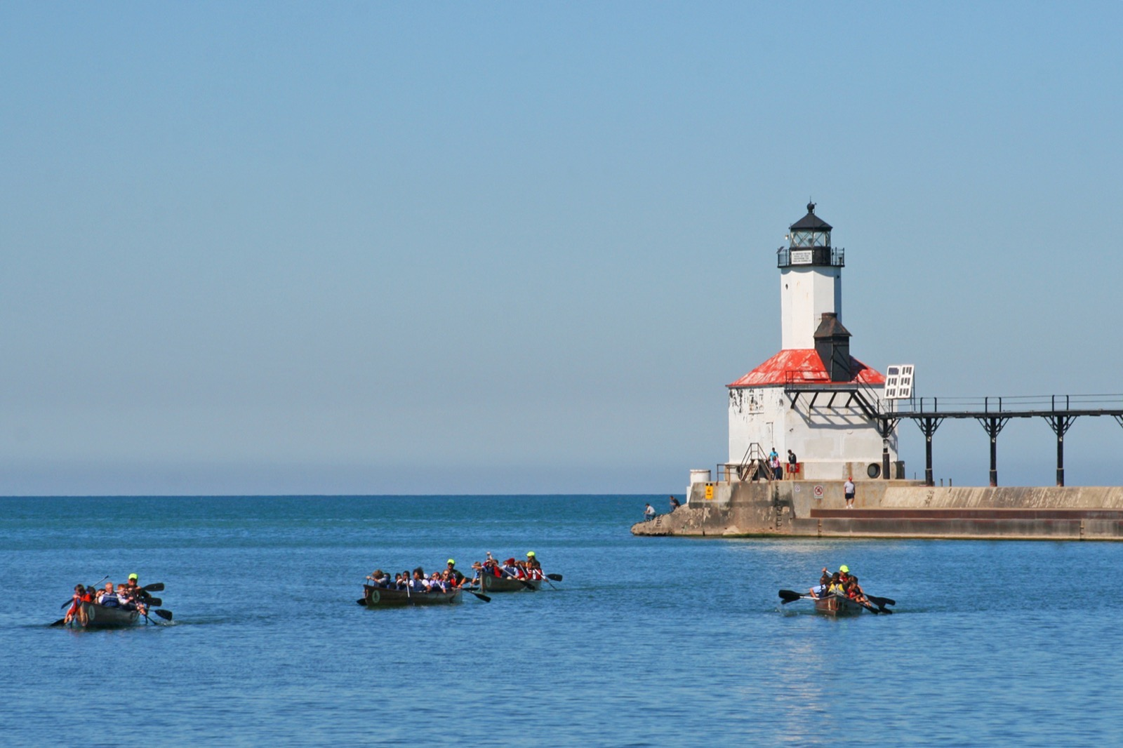 four canoes head back towards the landing, paddling away from the lighthouse