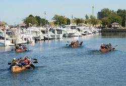 four canoes in the marina next to large boats