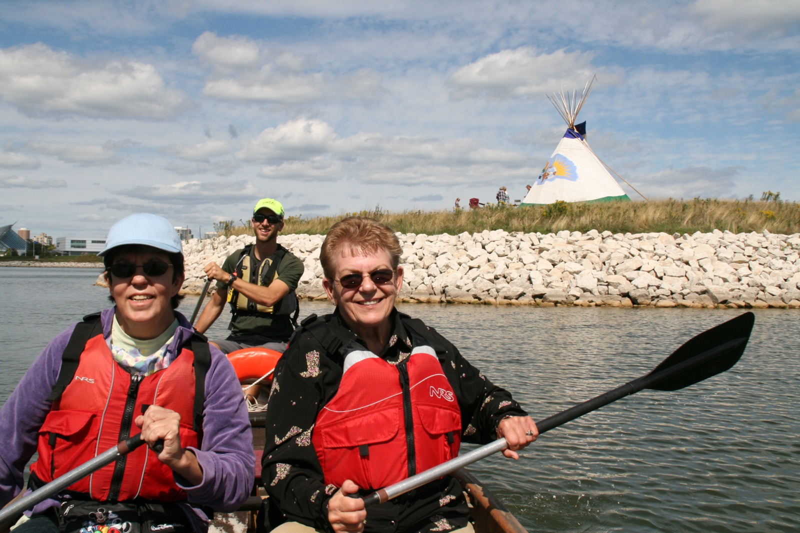two women smiling as they paddle along the river there is a tepee along the shore in the background