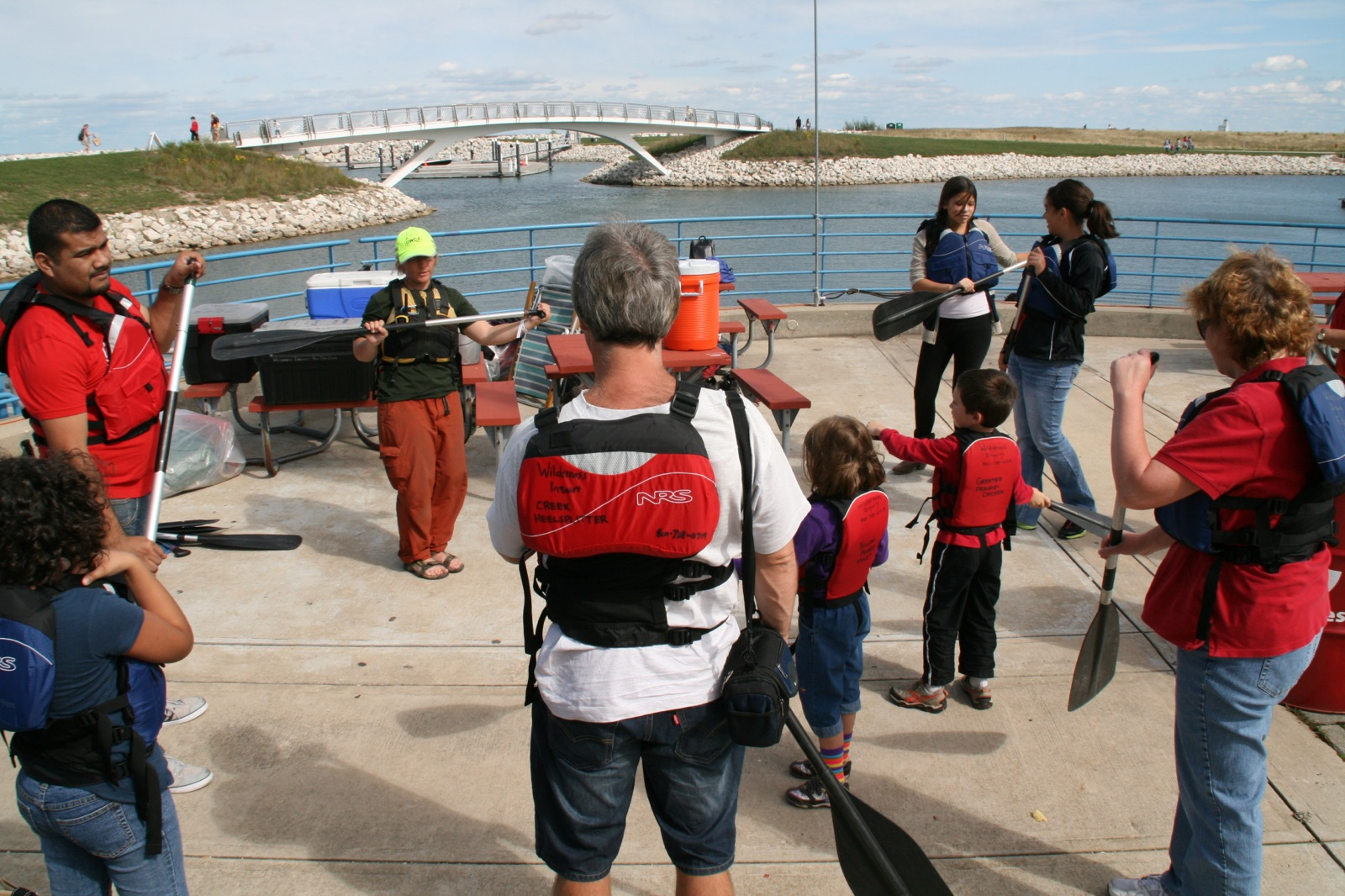 Participants stand on land next to the river learning paddling techniques