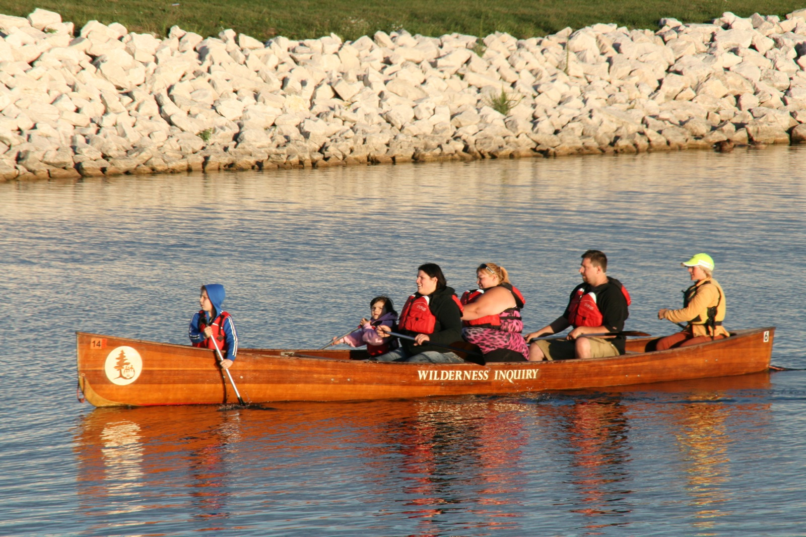 group of 7 paddle their canoe along the water near a rocky shore