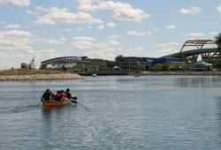 photo of a group paddling the canoe away from camera towards buildings along the shoreline
