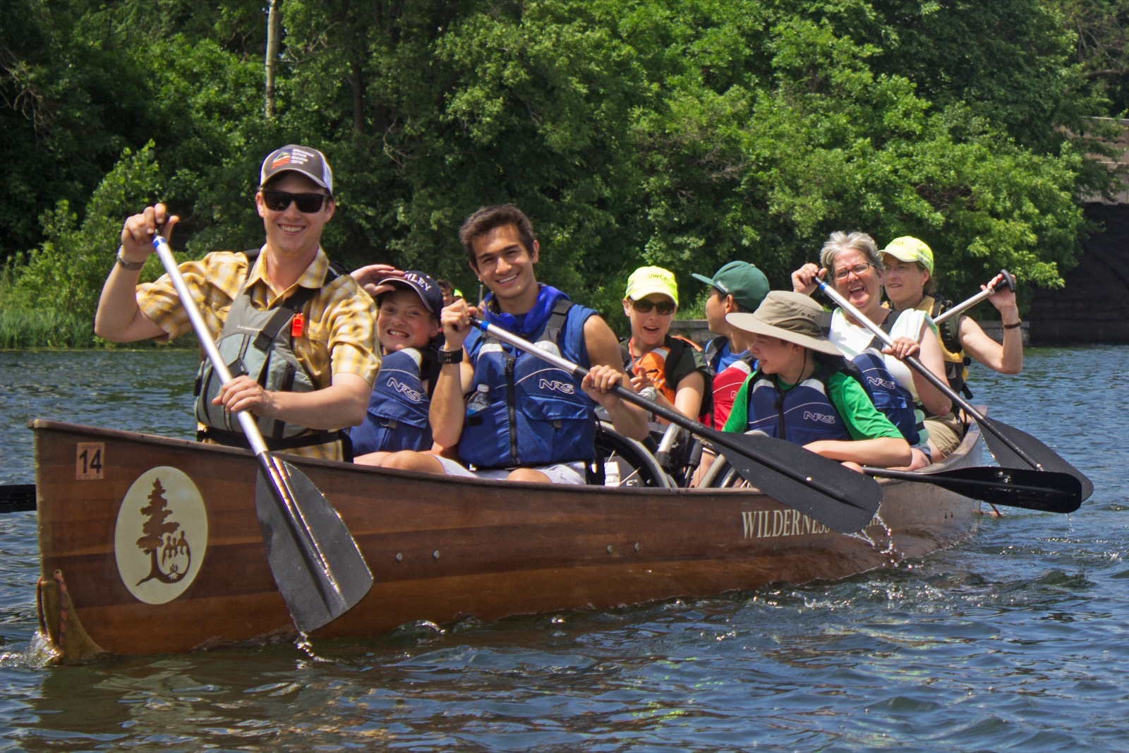 Participants smile for the camera as they canoe in a Voyageur.
