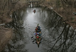 On a fall day, three boats of participants canoe along a narrow waterway between two of the lakes in the Chain of Lakes.