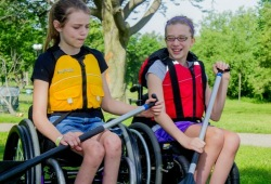 Two girls in wheelchairs learn how to use a paddle on land before setting off on a paddling adventure.