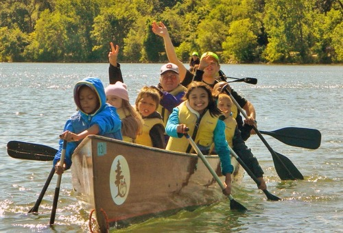 A Voyageur canoe full of young students waves at the camera as they paddle across a lake with bright green trees in the background.